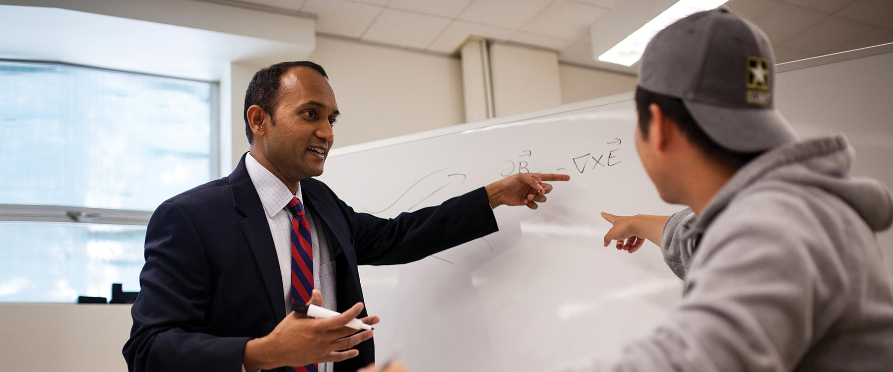 Professor Kamesh Sankaran stands across from a biophysics student talking. Both point toward an equation on a whiteboard.