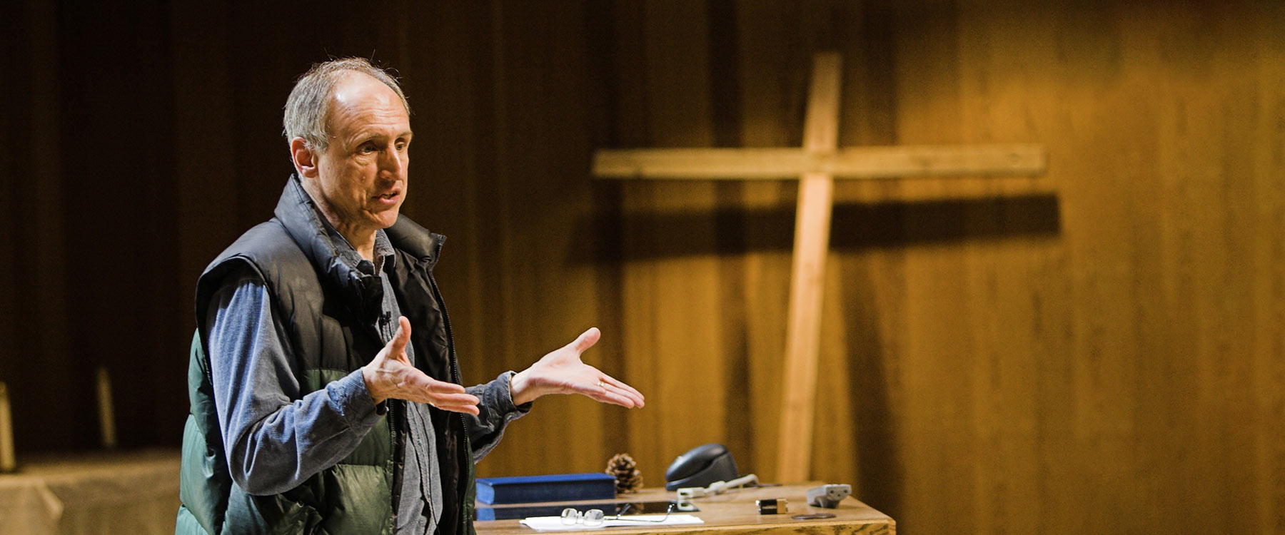 Professor Jerry Sittser gestures with outstretched hands as he presents a theology lecture in the chapel.
