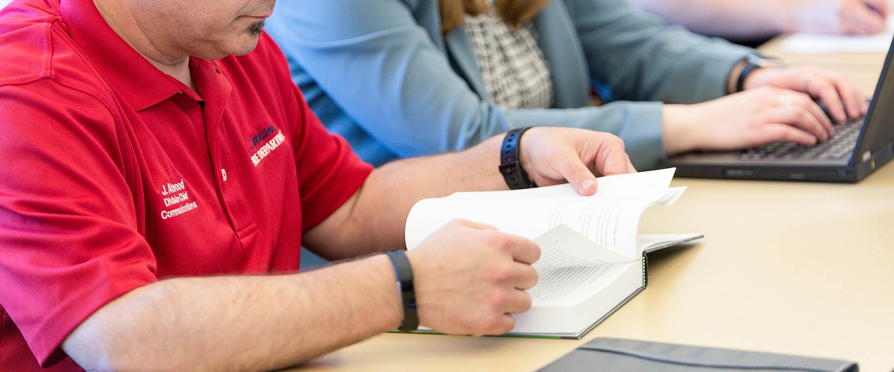 A student looks down at a book and flips through the pages. Next to him, a student types on a laptop.