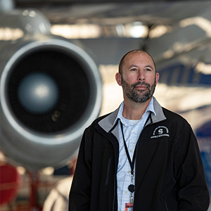 Jeff Mitchell stands in front of an airplane.