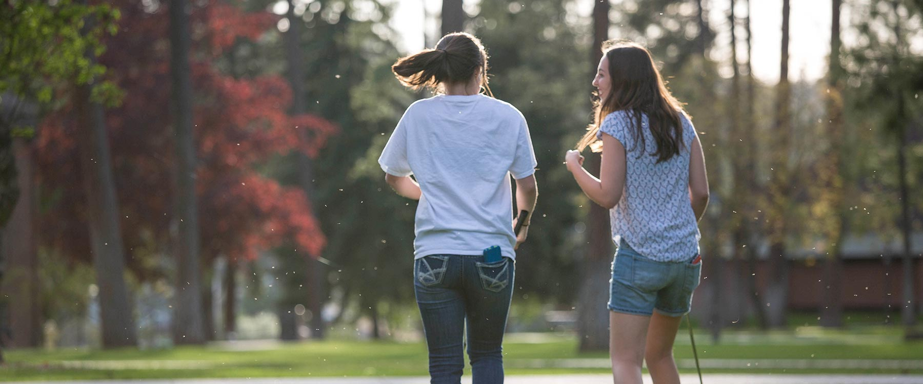 Two female students, with backs to the camera, walk across the middle of campus and turn toward each other laughing.