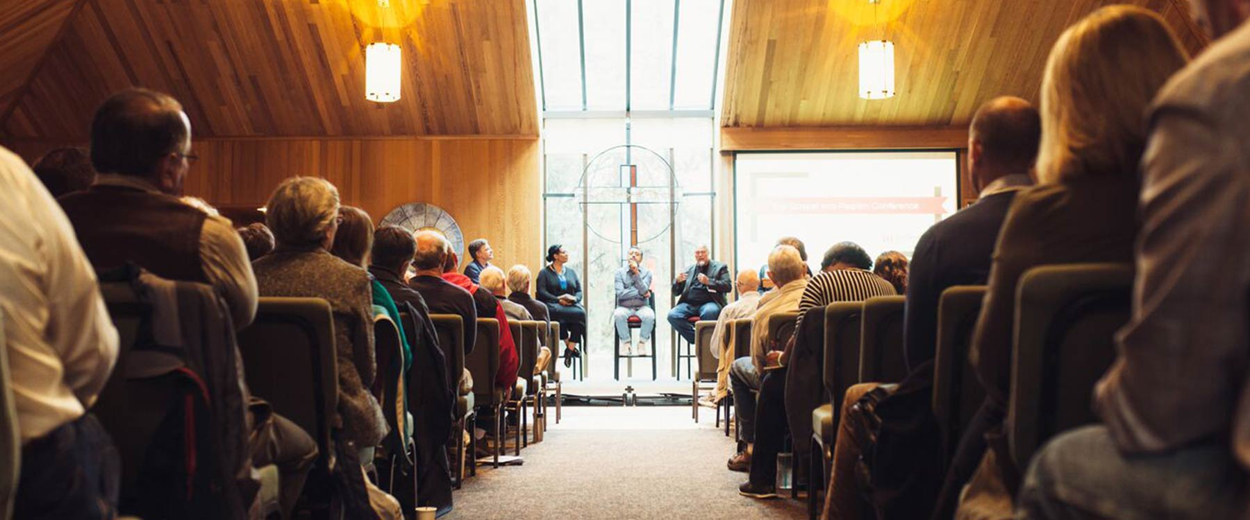 A panel of speakers sits at the front of the university chapel. The rows of seats are filled with listeners.