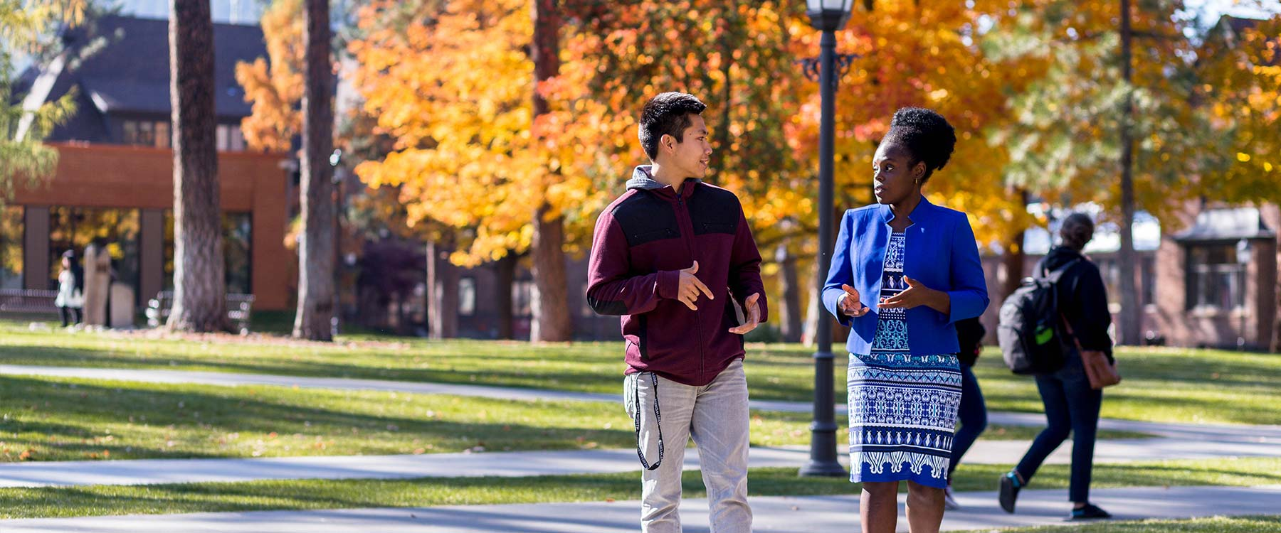 Professor Ndichu talks with a student while walking on campus. They turn toward each other talking.