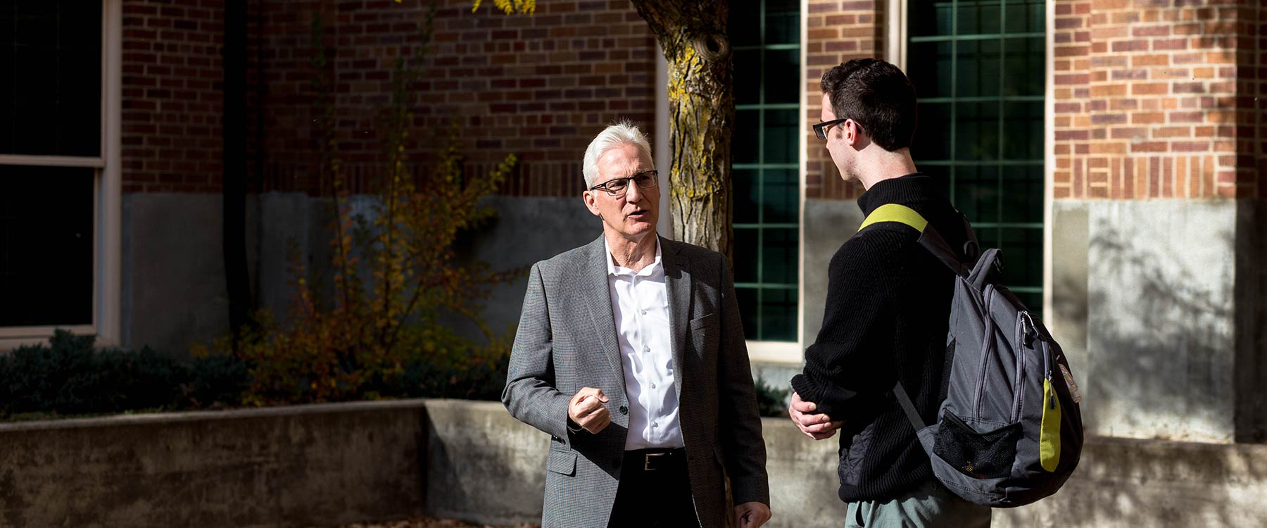 Professor Randall Michaelis stands and speaks with a student somewhere outside a campus building.