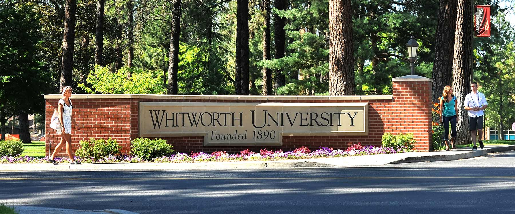 Students walk on the sidewalk on either side of the brick Whitworth entrance sign.