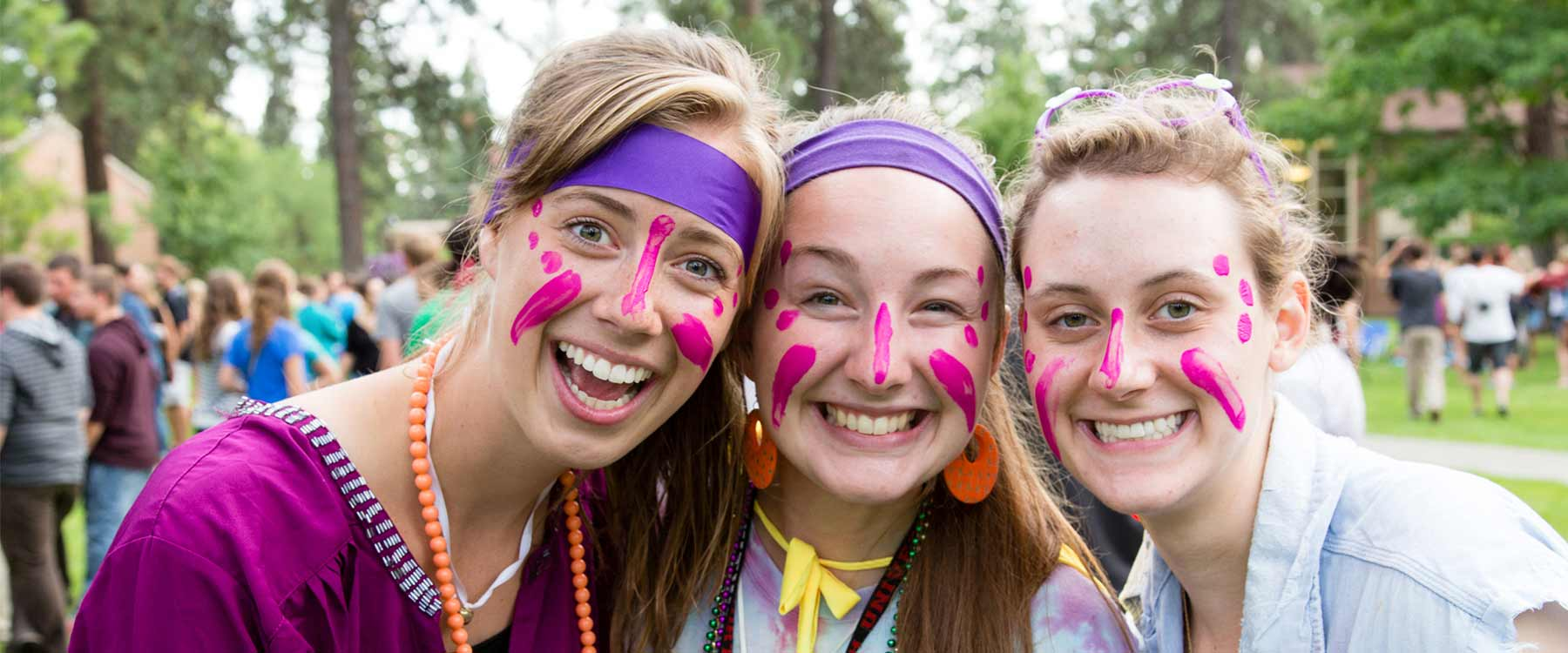 Three students, with headbands and bright face pain, stand close together and smile.