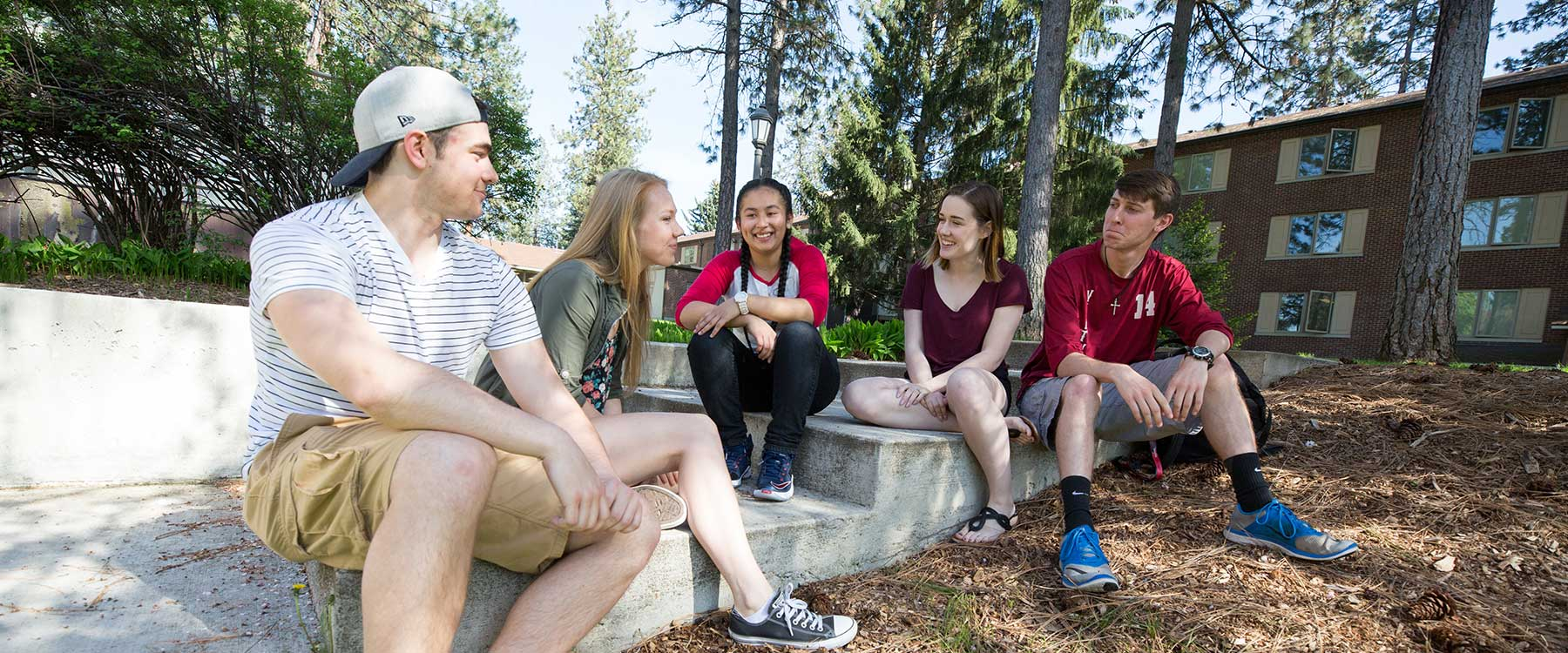 A group of students sit on concrete steps somewhere on campus. They smile and talk together.