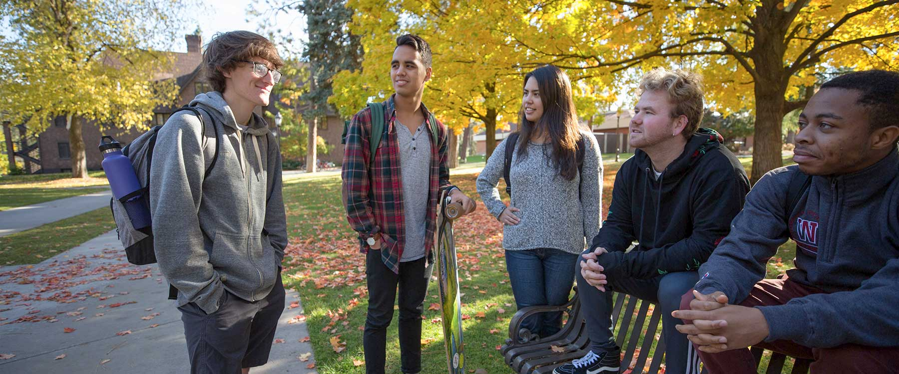A group of students talk with one another while on campus.