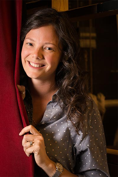 Brooke stands partially behind a red stage curtain and smiles.