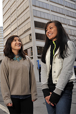 Camina and Winnie stand on a street corner in downtown Spokane. They turn toward each other laughing.