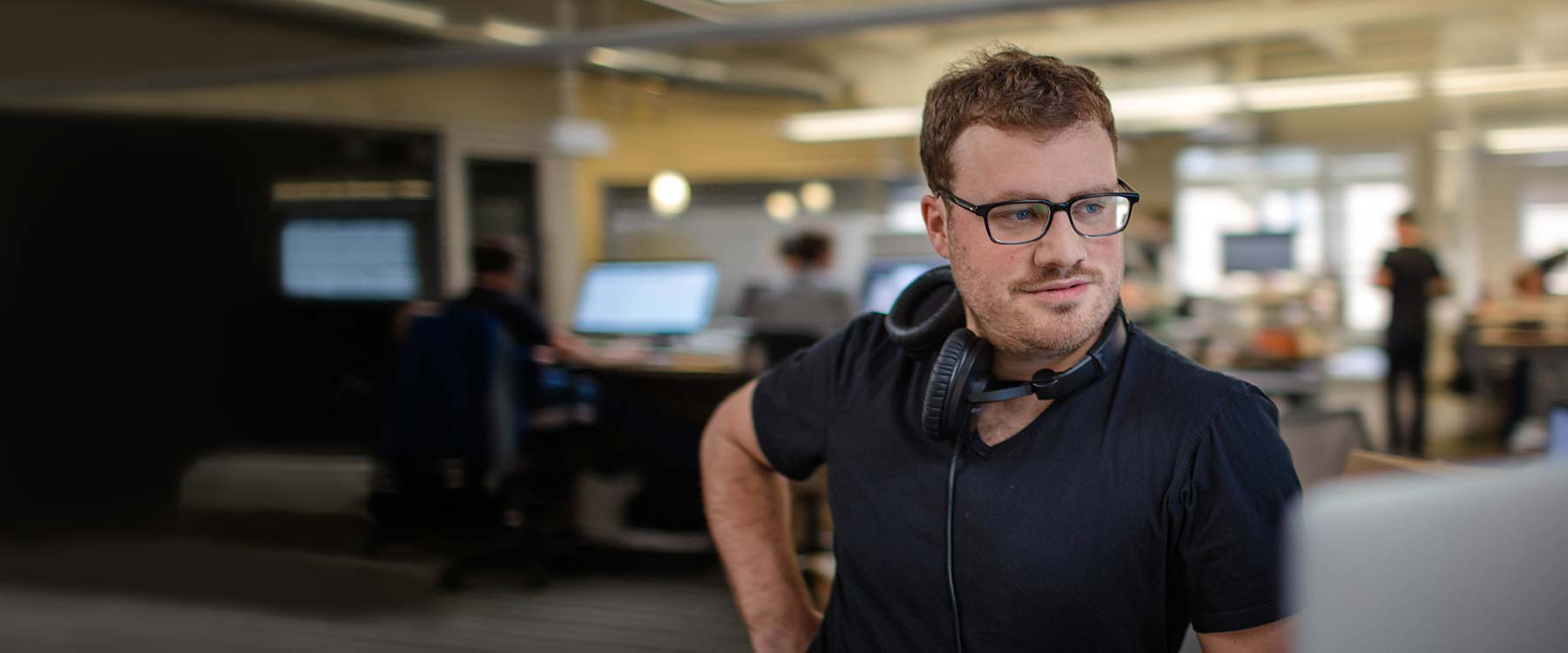 Chris leans against a desk and looks toward a computer screen. He wears headphones around his neck.